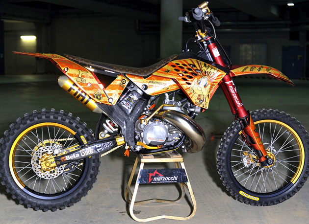 Instead of the KTM orange, Vanni opted to go for a blingin' red chrome, gold glitter, black and orange getup, with the addition of red Marzocchi forks and a custom Luis Vuitton seat. It's nearly impossible to find one non-aftermarket part on the thing.