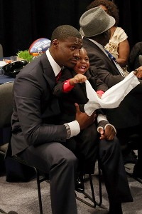 Morris Claiborne and his son sit in the greenroom at the NFL draft. Morris Jr. snuck into more than one draft day photo.