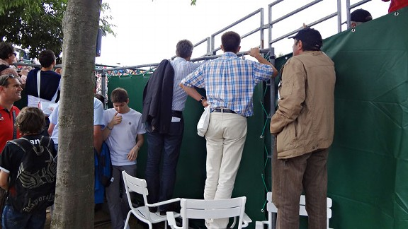 Fans try to sneak a peek at ongoing matches by standing on chairs to look inside the court.