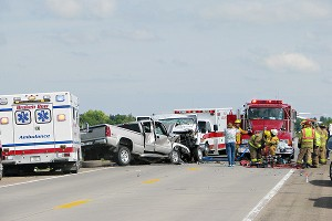 Emergency teams work at the scene of the crash on Highway 2 near Ansley, Neb.