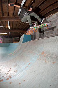 Marisa kickflip-to-pivots an indoor quarterpipe