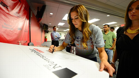 Morgan puts her autograph on a sign at a luncheon for ESPN employees.