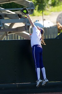 Kylee Lahners goes over the fence to take away a home run during Washington's 1-0 victory against the Missouri Tigers.