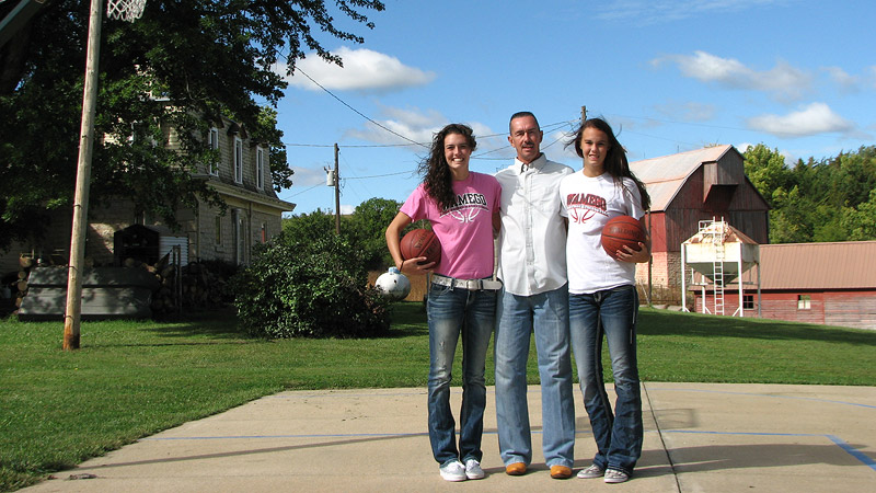 Kaylee, Lanie and Jim Page standing on their backyard basketball court.
