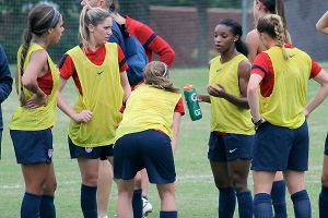 USWNT players, including Morgan Brian (second from left) listen to Crystal Dunn (with water bottle) during Friday's practice.
