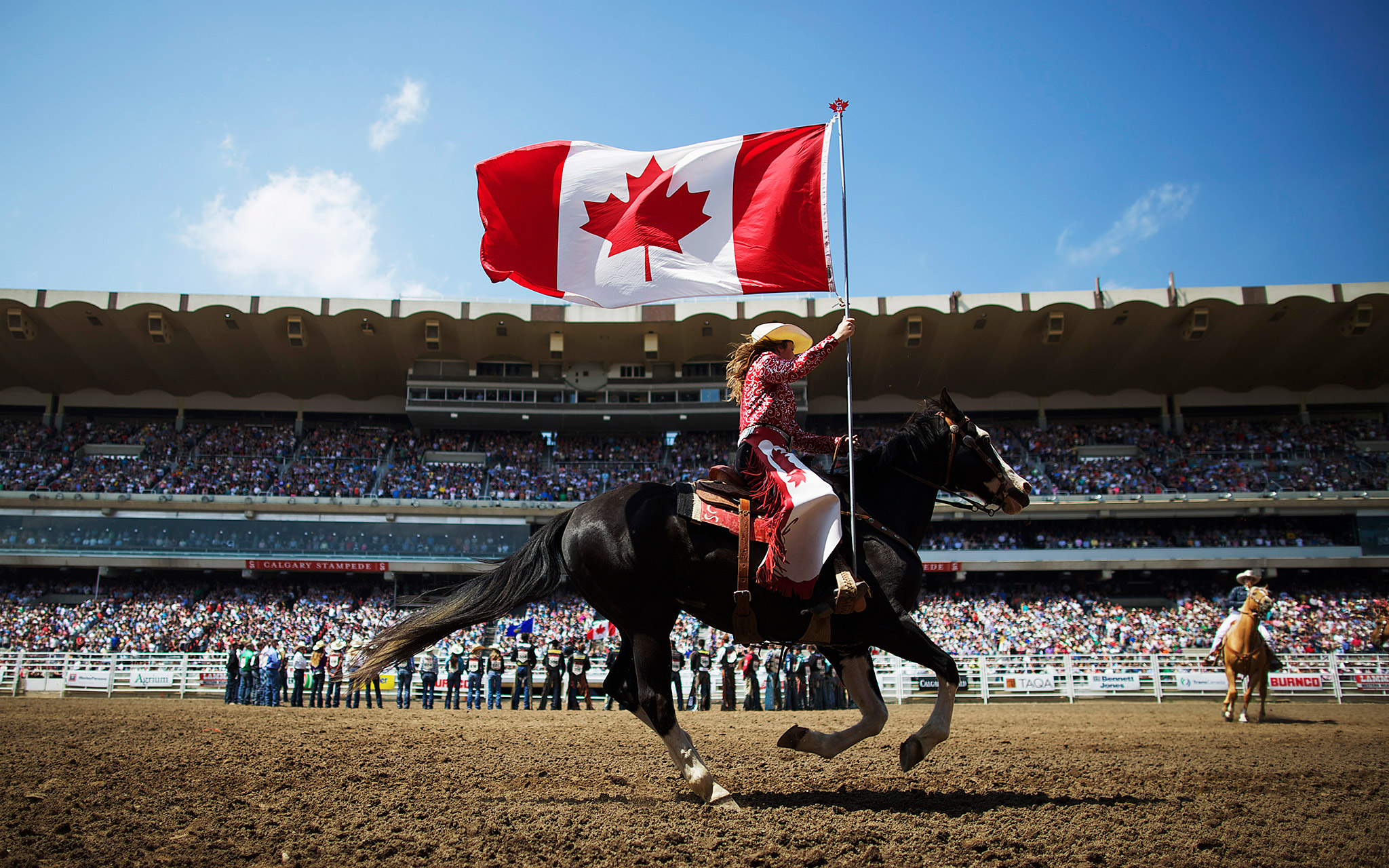 A rodeo girl carries the Canadian flag during the singing of the national anthem during Day 2 of the Calgary Stampede rodeo in Calgary, Alberta.