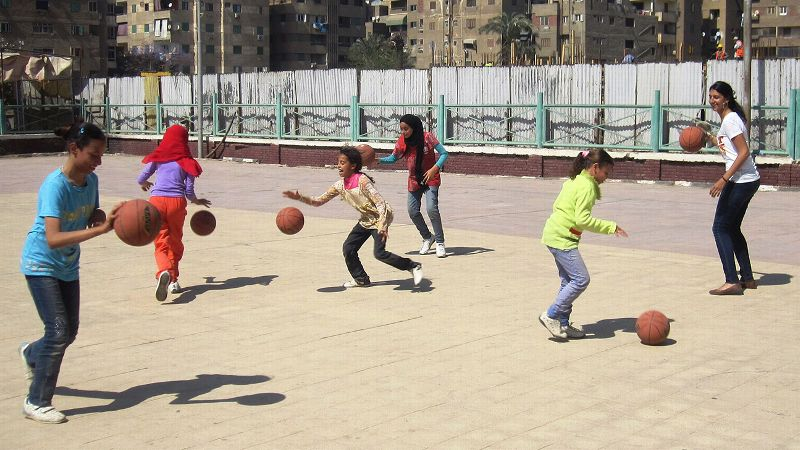 Educate-Me founder Yasmin Helal plays basketball with girls in a program run by a fellow Global Sports Mentorship Program participant.