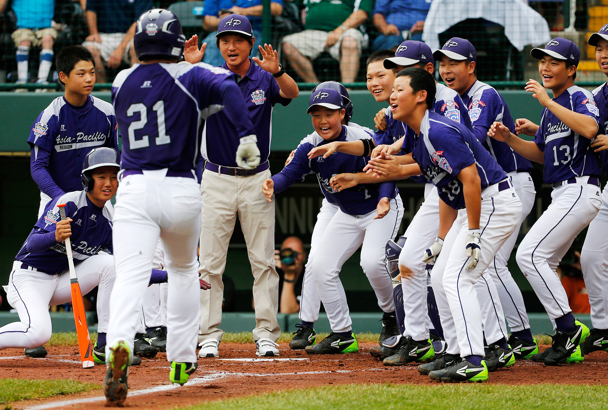 The smiles say it all as Hae Chan Choi of Seoul, South Korea, crosses home plate after hitting a two-run home run against Tokyo, Japan, at the Little League World Series.