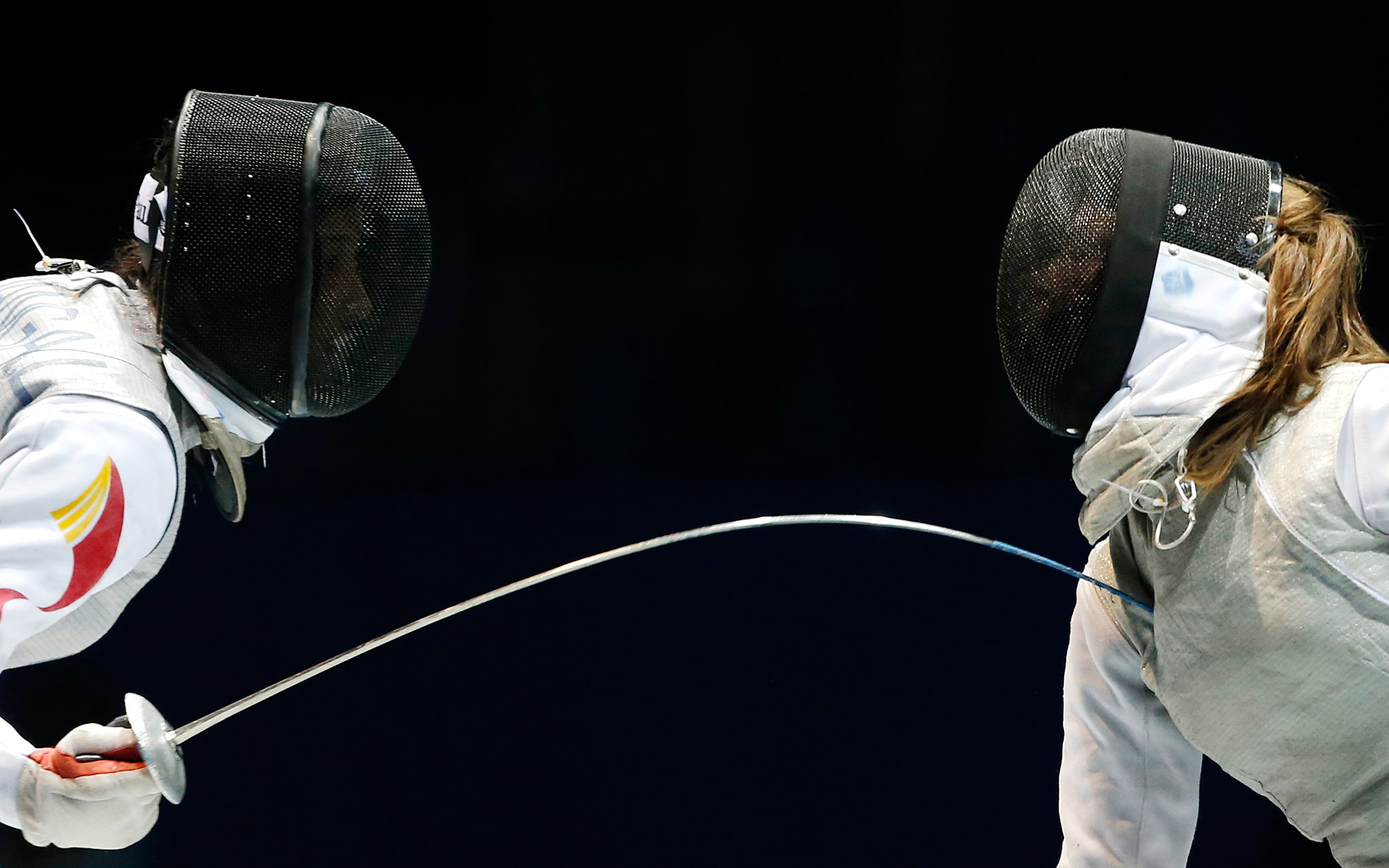 China's Huang Ali, left, and Russia's Marta Martyanova compete during the women's individual foil at the 2014 Nanjing Youth Olympic Games.