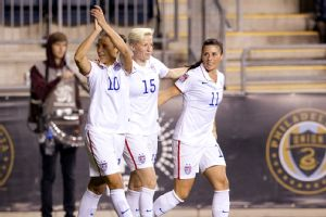 Carli Lloyd (10), Megan Rapinoe (15), and Ali Krieger (11) celebrate after Lloyd's goal in the first half against Mexico in a 2014 CONCACAF Women's Championship semifinal game.