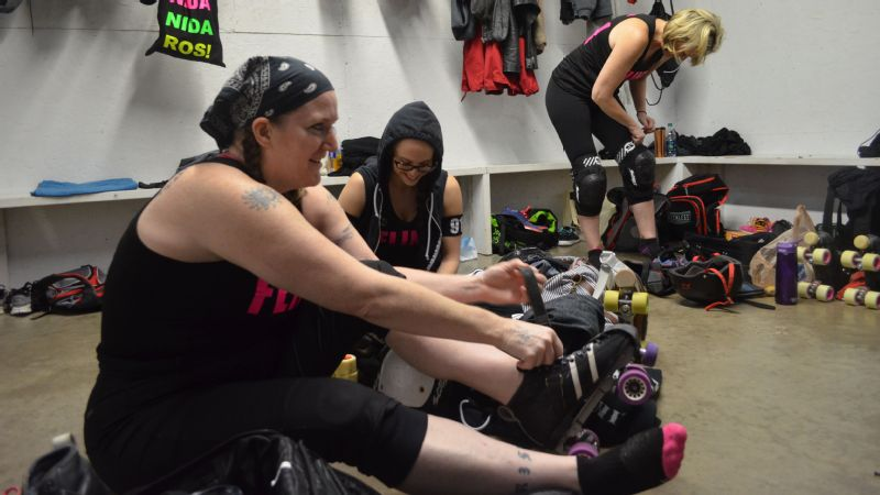 Rebecca Lopez, aka Cammie Flage, and Katie Fehr, aka Slapher Sally, strap on their gear in a makeshift locker room April 9.
