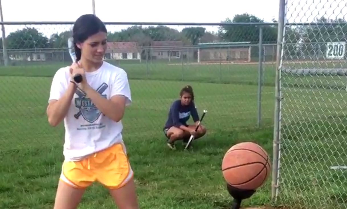 Softball player swings at basketball
