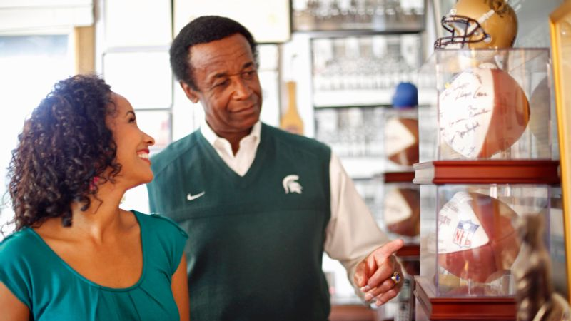 Maya and Gene Washington amid Michigan State memorabilia in East Lansing.
