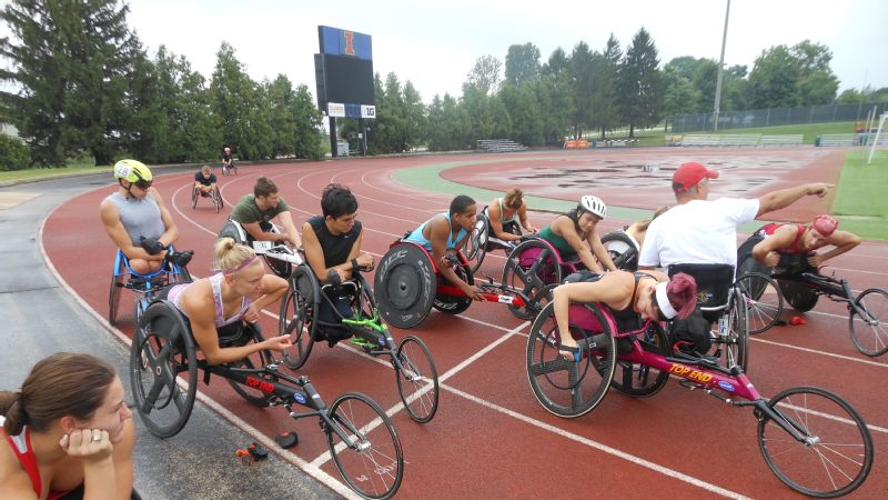 University of Illinois coach Adam Bleakney (in the white shirt and red hat) gives instructions on the next set of hard repetitions to the men and women on the University of Illinois wheelchair track team.
