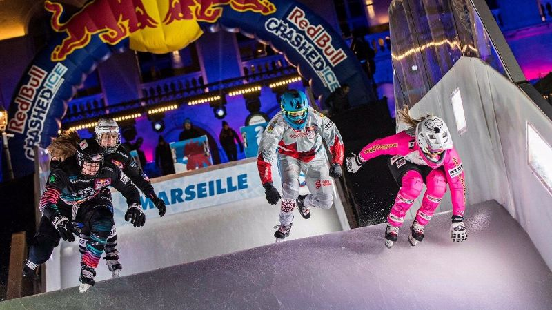 Jaqueline Legere, right, takes a leap off the steep, icy slope that leads to the crashed ice course.