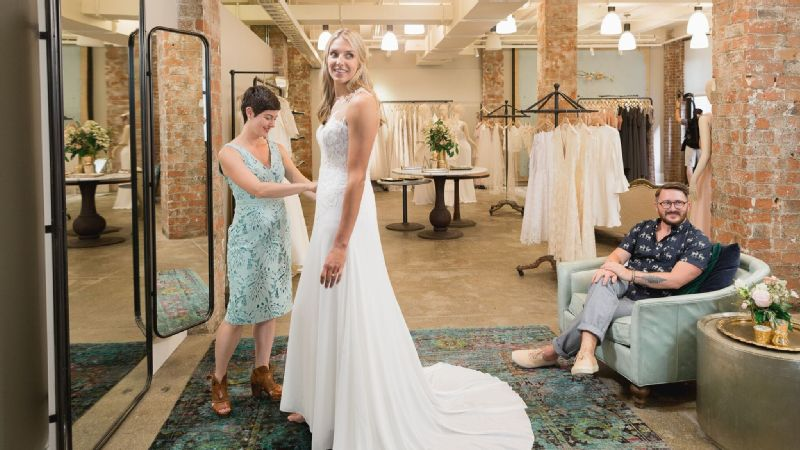 Delle Donne in a bridal gown at a wedding atelier.