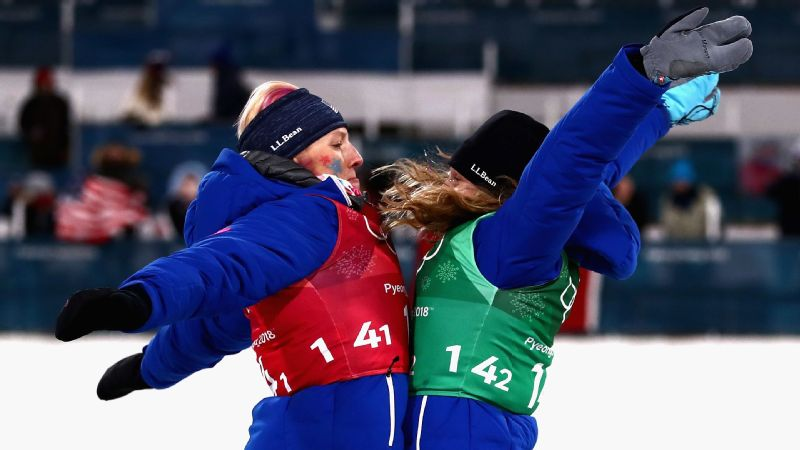 Kikkan Randall (left) and Jessica Diggins celebrate their cross-country team sprint success on the podium as they receive their gold medals.