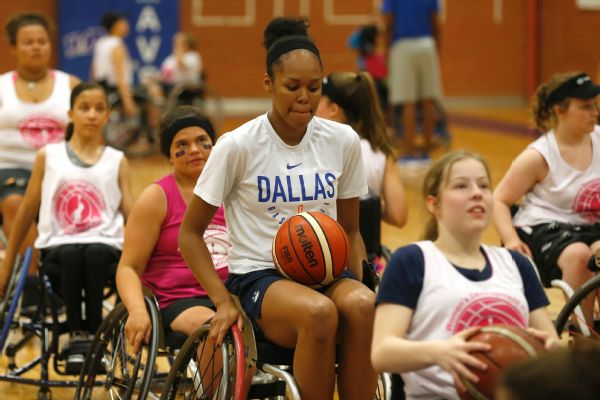 Dallas Wings rookie Azura Stevens does shooting drills with the Lady Mavs women's wheelchair development campers.