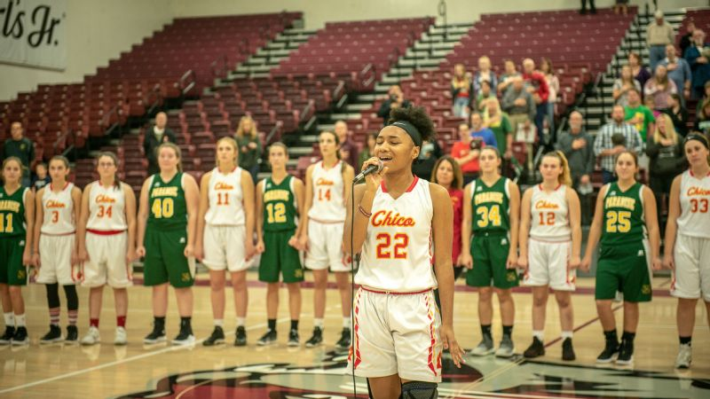 The Paradise girls' basketball team stands together with Chico High School for the national anthem before their game on Nov. 26. It was the first game played after the horrific Camp Fire leveled the town of Paradise.
