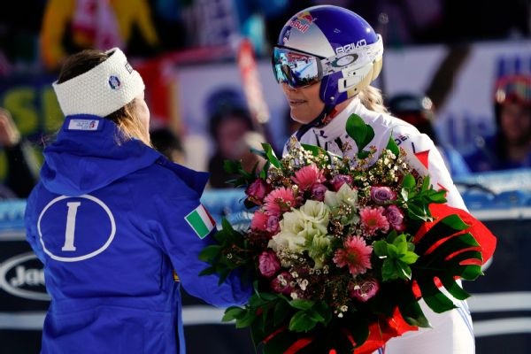 Lindsey Vonn receives a bunch of flowers from Italy's Sofia Goggia after completing a women's World Cup super-G in Cortina D'Ampezzo, Italy.